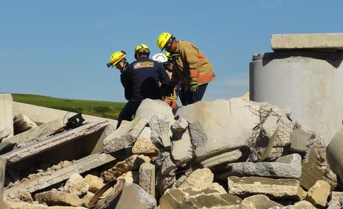 """Rescue workers with the Fairfax County (Virginia) Fire and Rescue Department pull a buried """"victim"""" out of rubble after using a new technology called FINDER developed by NASA and the U.S. Department of Homeland Security."""