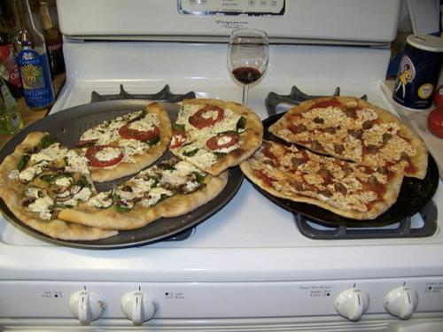 """""""Two pizzas sitting on top of a stove top oven,"""" is how a Google program described this image."""