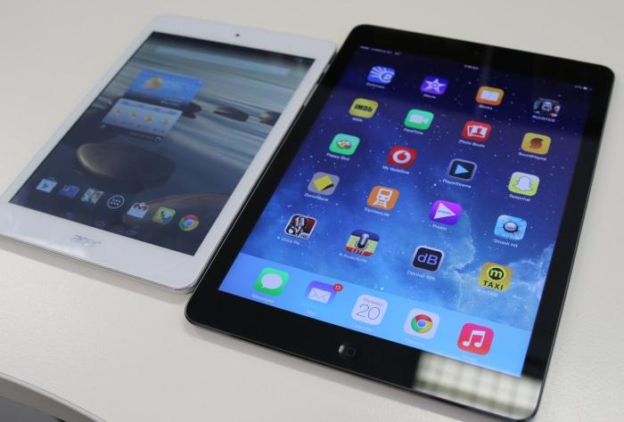 The white Acer alongside a black, full-sized iPad Air