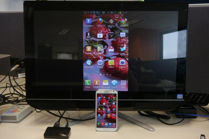 Miranet in action, showing the contents of the Samsung Galaxy Note II on the big screen via the Push2TV adapter that's visible in the lower left-hand corner.